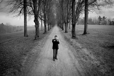 Trumpeter Doug Woolverton is photographed by fine art photographer David Lee Black on a tree lined road in Massachusetts.