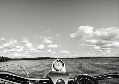 Fine art photographer David Lee Black's Road King Harley Davidson with open field, clouds and sky.