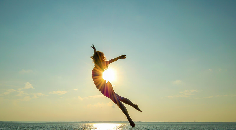 Fine Art photographer David Lee Black portrait of ballet dancer, yoga teacher Heather Brown flying through the sun with health, wellness and spirituality.