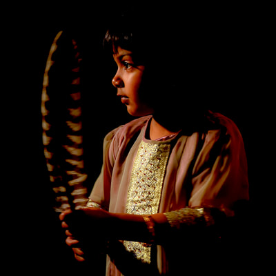 Indian girl holding hawk feather photographed by David Lee Black.