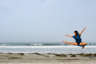 fine art photographer David Lee Black with color photograph of model ballet dancer leaping next to Atlantic ocean beach with sky, waves, and sky.
