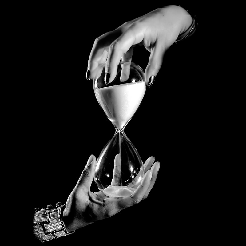 Noted Boston fine art photographer David Lee Black photographs surrealism hands with hourglass symbolizing time.