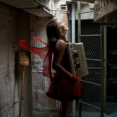 Fine Art photographer David Lee Black portrait of Meghan Kallman with accordian, red wings near ladder of Superman Building, Providence, Rhode Island. Abandoned spaces.