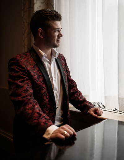 Fine Art photographer David Lee Black portrait of pianist Nick Sanfilippo next to grand piano of Biltmore Hotel, Providence, Rhode Island. Red smoking jacket looking out window.