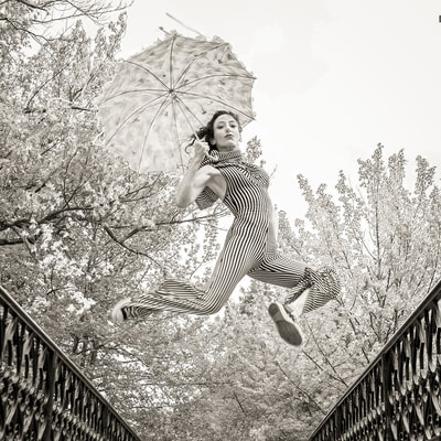 Fine art photographer David Lee Black 's black and white photograph of model with umbrella and converse sneakers jumping at Roger Williams Park, Providence, Rhode Island.