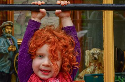 fine art photographer David Lee Black with red hair irish lass hangin from bar in Ennistimon, County Clare, Ireland.